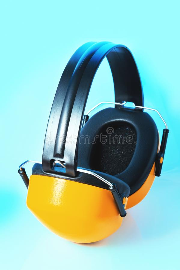 Yellow headphones against noise on blue background royalty free stock photography
