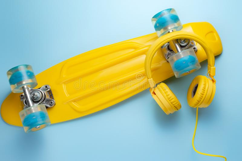 Yellow headphones and skateboard or pennyboard on blue background. Music concept. stock photography