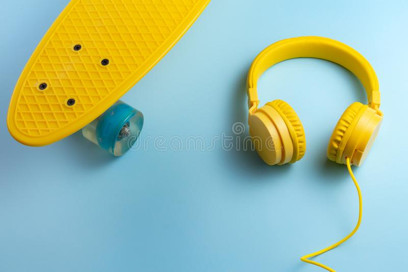 Yellow headphones and skateboard or pennyboard on blue background. Music concept. royalty free stock image