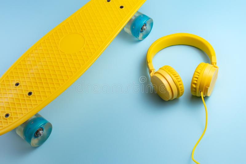 Yellow headphones and skateboard or pennyboard on blue background. Music concept. stock image