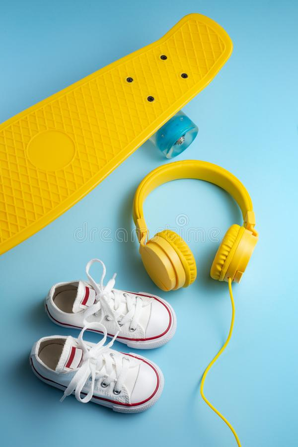 Yellow headphones, white sneakers and traditional style soccer ball over yellow background. stock image