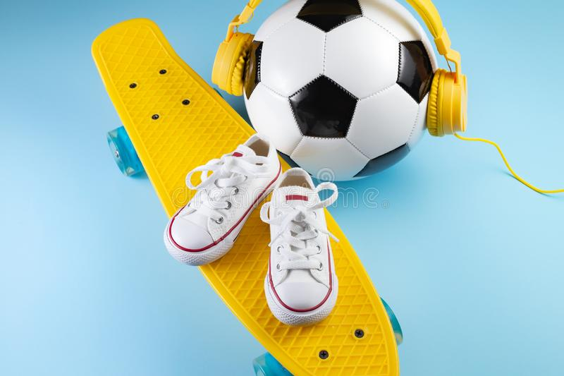 Yellow headphones, white sneakers and traditional style soccer ball over yellow background. royalty free stock photos