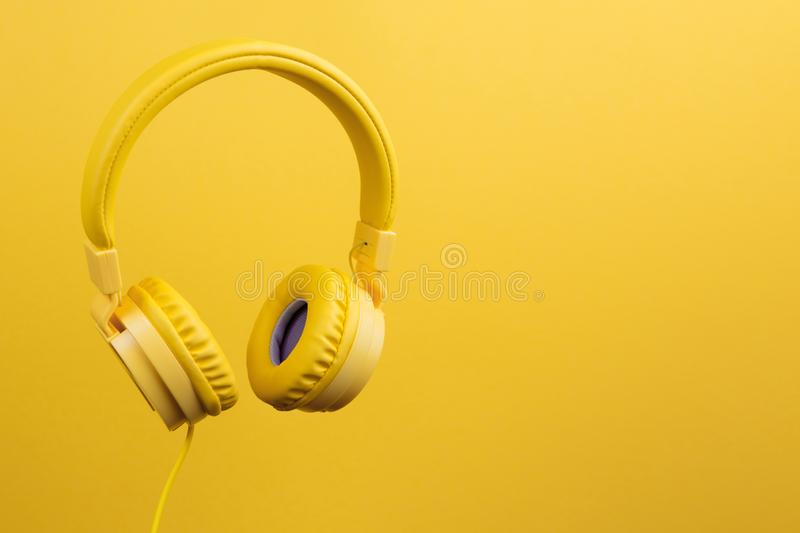 Yellow headphones on yellow background. Music concept. royalty free stock photo