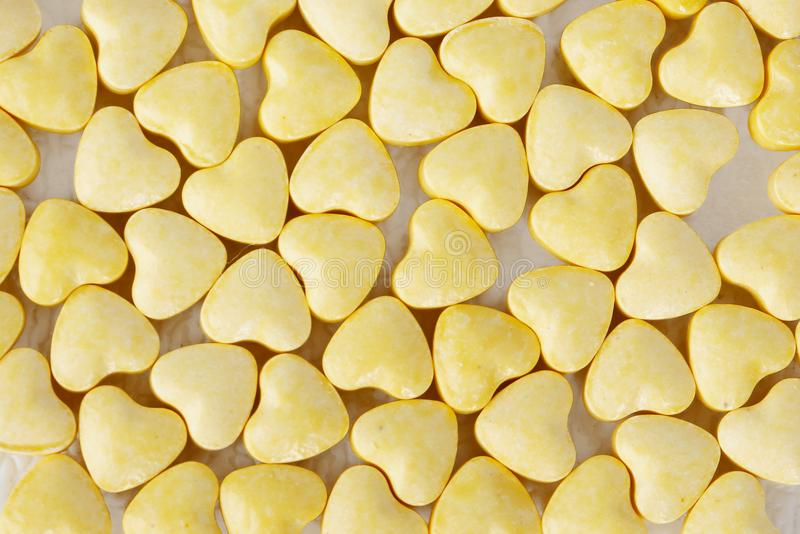 Yellow heart shaped pills royalty free stock images