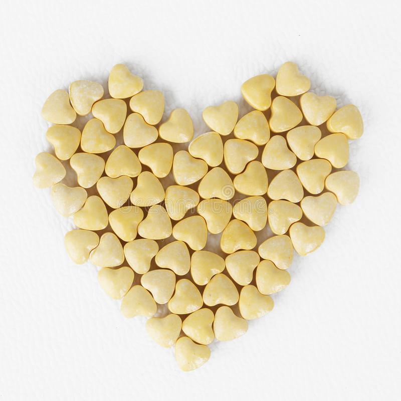 Yellow heart shaped pills royalty free stock photo