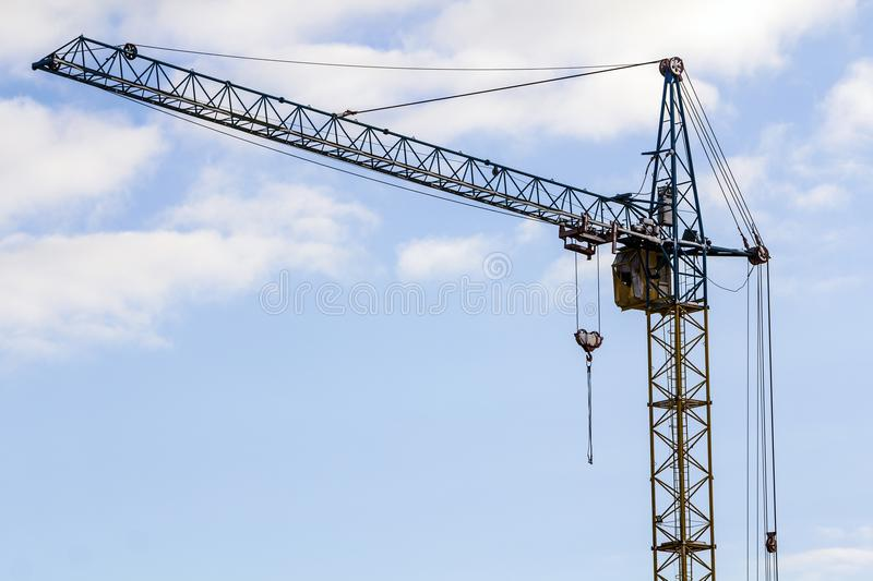 Yellow heavy duty industrial tower construction crane against bl royalty free stock photos