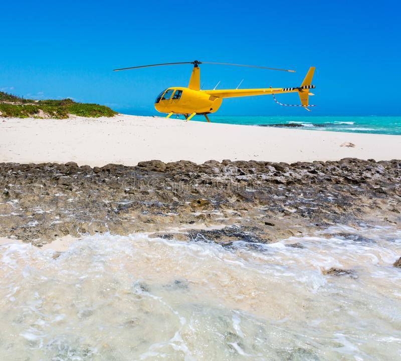 A yellow helicopter landed on idyllic empty sandy beach of remote island, azure turquoise blue lagoon, New Caledonia, Oceania. royalty free stock photo
