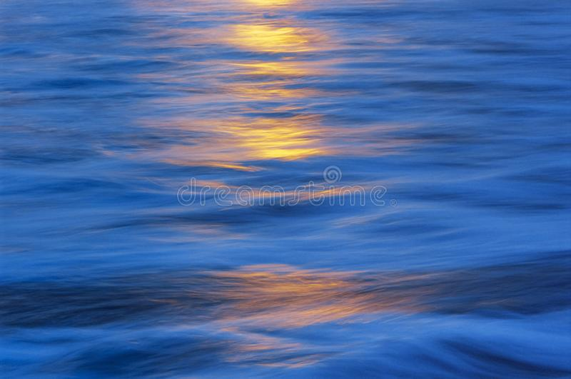 Yellow highlights on blue water. Yellow highlights reflected on moving blue water royalty free stock photos
