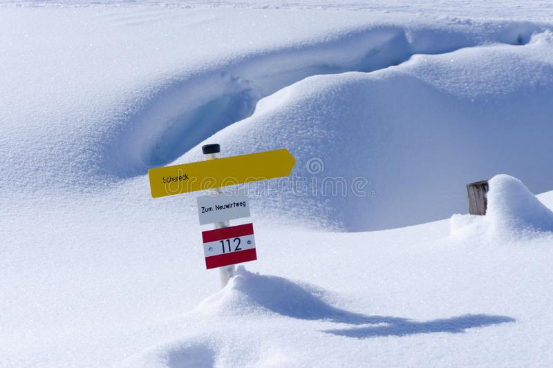 Yellow hiking sign in the snow of austria royalty free stock photography
