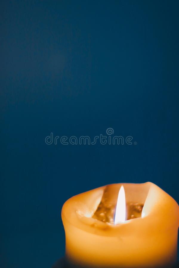 Yellow holiday candle on blue background, luxury branding design and decoration for Christmas, New Years Eve and Valentines Day royalty free stock photo