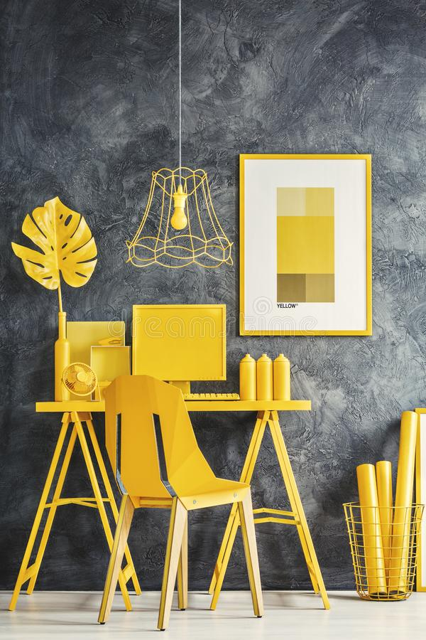 Yellow home office. Yellow chair, desk, poster, plant, computer and decorations in home office interior with gray wall royalty free stock photo
