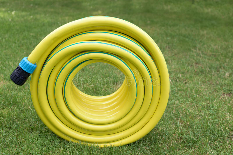 Yellow hosepipe in the garden stock images