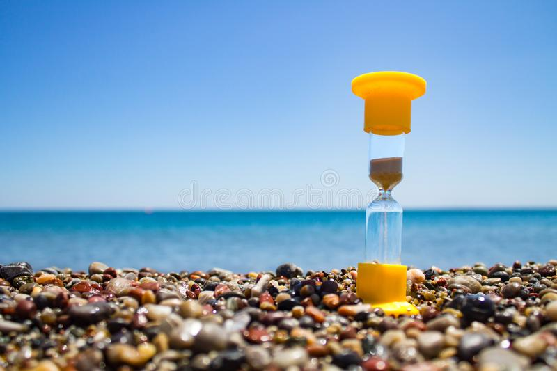 Yellow hourglass with crumbling sand standing on the wet sea pebbles with the sea and the clear sky in the background stock photography