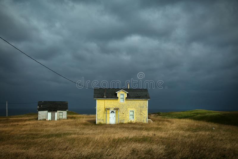 Yellow house with a dark grey sky. Old fisherman house with yellow tiles in a dark grey sky in iles de la madeleine in Canada stock images