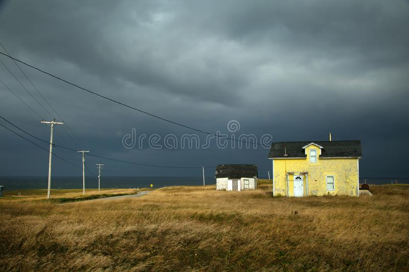 Yellow house with a dark grey sky. Old fisherman house with yellow tiles in a dark grey sky in iles de la madeleine in Canada royalty free stock photo