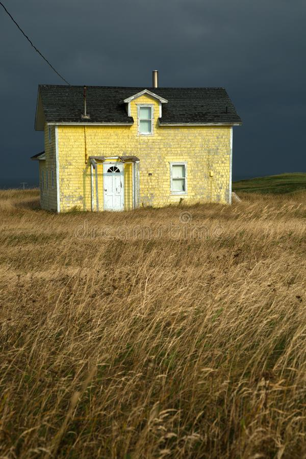 Yellow house with a dark grey sky. Old fisherman house with yellow tiles in a dark grey sky in iles de la madeleine in Canada royalty free stock images