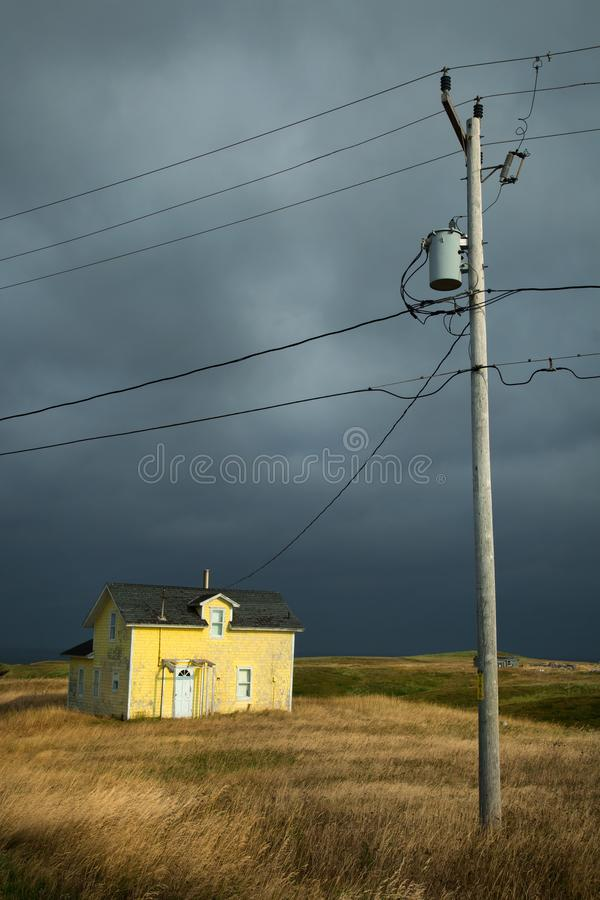 Yellow house with a dark grey sky. Old fisherman house with yellow tiles in a dark grey sky and a lamp post in iles de la madeleine in Canada stock images
