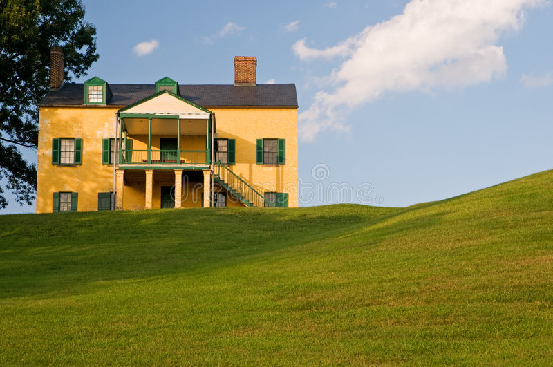 Yellow House On Grassy Hill Stock Image