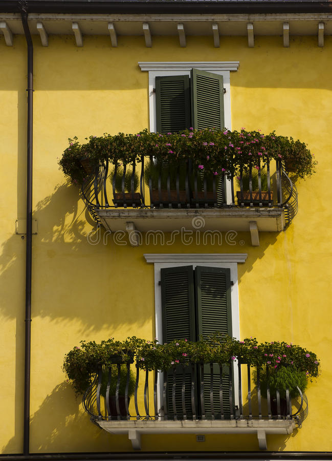 Yellow house green shutters decorated balconies stock photo