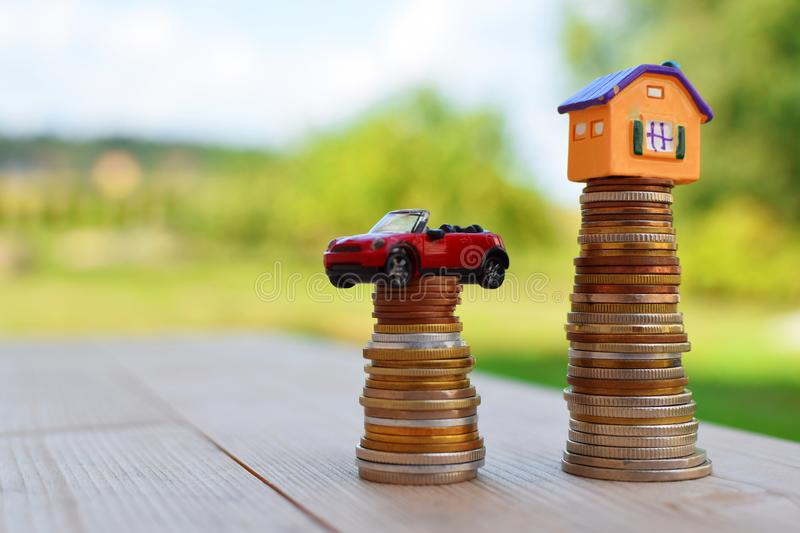 Yellow house and red car on coins stack royalty free stock image