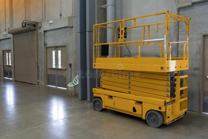 Yellow hydraulic scissor platform stand by for service and maintenance in factory work area. royalty free stock photos