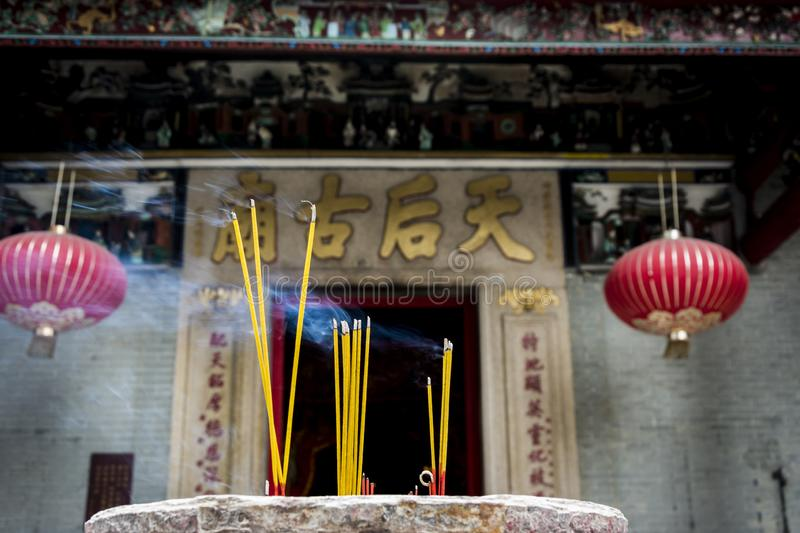 Incense sticks burning at a Taoist temple in Hong Kong. Yellow incense sticks burning at a Taoist temple in Hong Kong stock photo