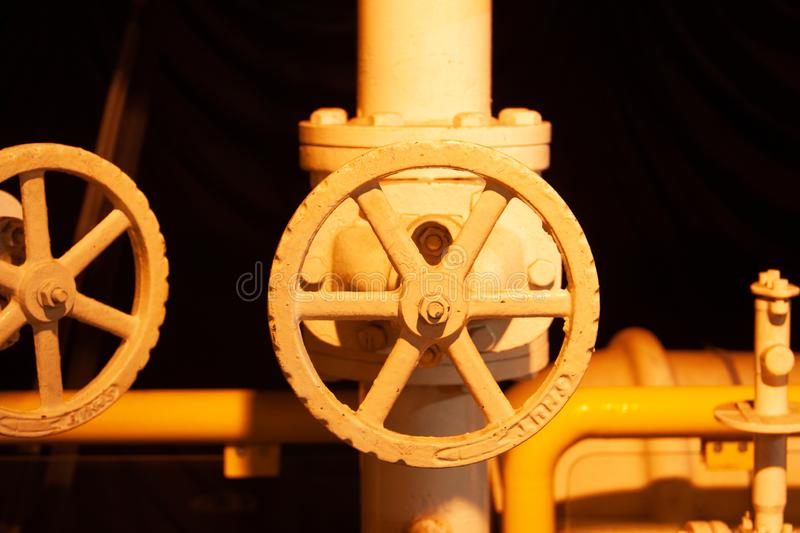Yellow industrial pipeline with valves close-up on dark background. Pipeline equipment, fuel plant industry. stock photos