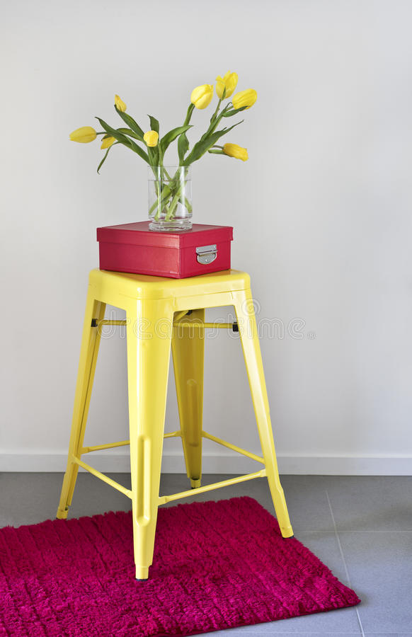 Yellow industrial stool and red rug. Home decor elements Yellow industrial stool and red rug with shoe box and tulips royalty free stock photography