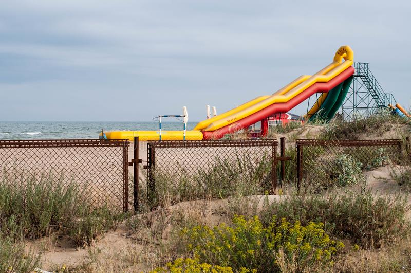 Yellow inflatable slide on beach sand stock image