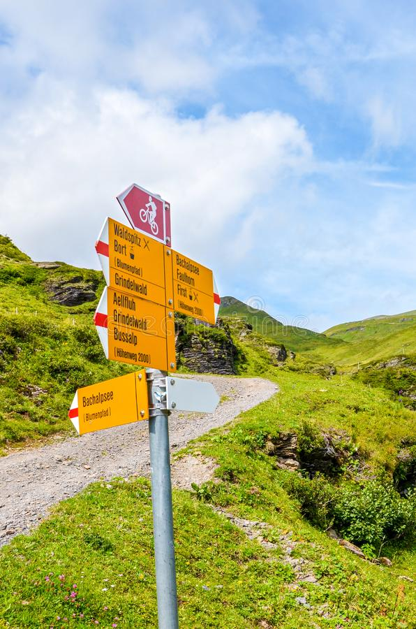 Yellow information sign on the path from Grindelwald leading to Bachalpsee lake in Switzerland. Tourist sign giving directions to. Hikers and cyclists in the royalty free stock photography