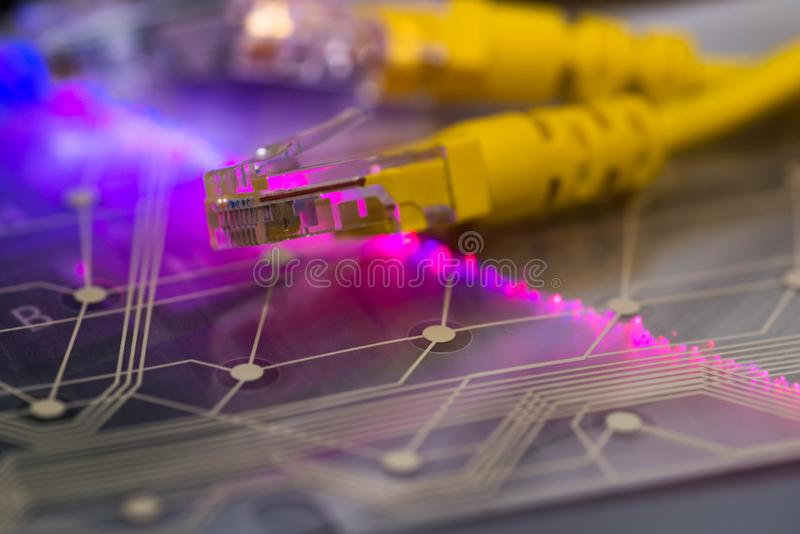 Yellow internet switch, plastic circuit board, glowing optical fibres on laptop keyboard stock photos