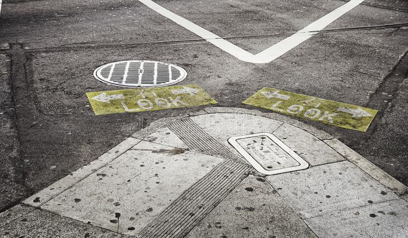Street warning signs `Look`. Yellow-ish and graphic signs on the asphalt to warn pedestrians to look right and left before crossing the street San Francisco royalty free stock photography