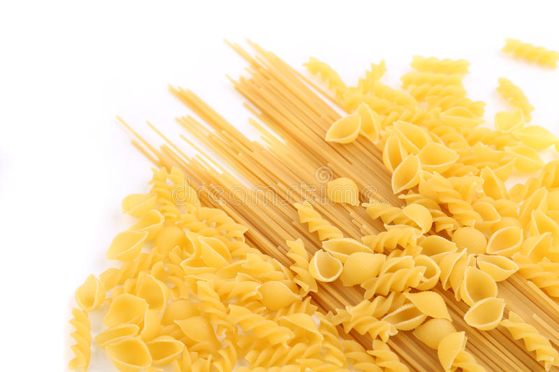 Yellow Italian pasta in different forms. On white background royalty free stock image
