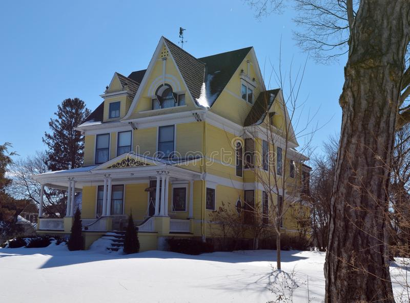 Yellow Italianate in Snow. This is a Winter picture of a house in Sycamore, Illinois. The large yellow house built in 1896 is an example of the Italianate style stock photo