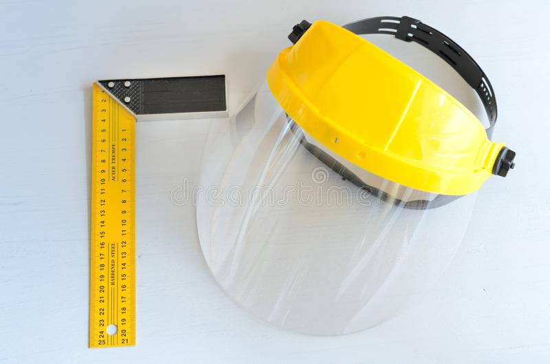 Yellow joiner`s ruler and face shield for home workshop royalty free stock image