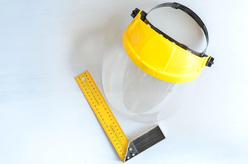 Yellow joiner`s ruler and face shield for home workshop.  royalty free stock photo
