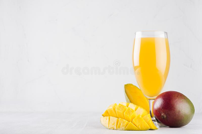 Yellow juice in elegant glass with ripe mango and sliced half on white wood board. Fresh exotic fruit drink. royalty free stock photography