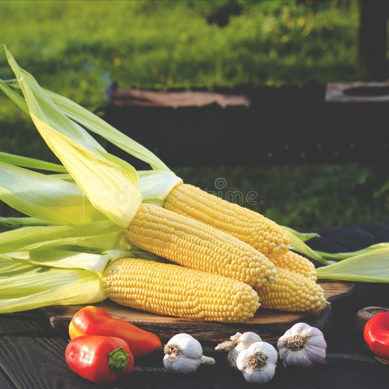Yellow juicy corn with green leaves lies on a wooden table in the summer garden against the backdrop of a grill stock image