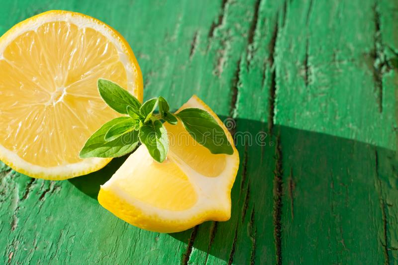 Yellow juicy lemon slices with mint leaves  on wooden green background with hard light, on strong sunlight with long dark shadow, stock photography