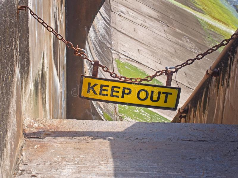 Yellow keep out sign hung on a chain blocking the entrance to concrete sea wall leading to the beach at high tide stock photography