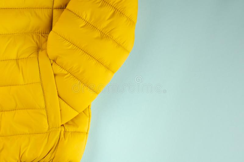 Yellow kids winter jacket composition on blue background. Flat lay, layout and tabletop mockup with copy space, above, flatlay, view, desk, frame, overhead royalty free stock images