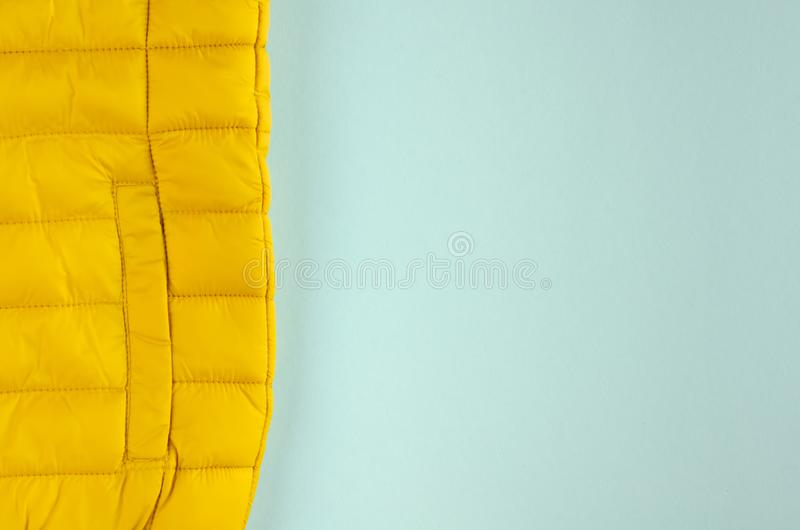 Yellow kids winter jacket composition on blue background. Flat lay, layout and tabletop mockup with copy space, above, flatlay, view, desk, frame, overhead stock image