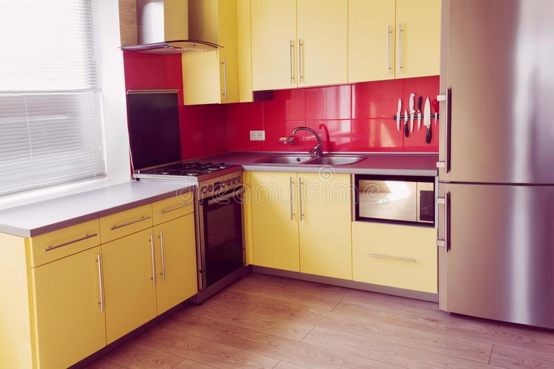 Yellow kitchen with red tiles. Yellow kitchen with cupboards with hinged doors, topped with a grey worktops and fitted with appliances including refrigerator royalty free stock images