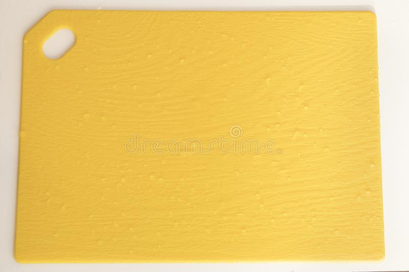 Yellow kitchen cutboard with waterdrops close up for background royalty free stock photography