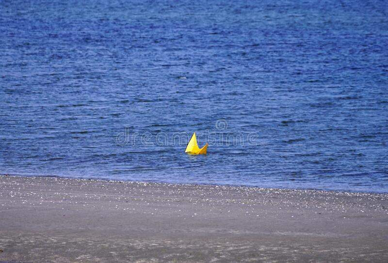 A yellow kite lost in the sea stock image
