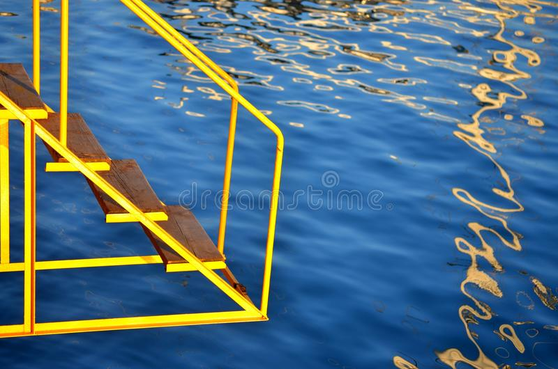 Yellow ladder to the sea. stock photos