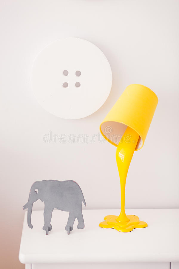 A yellow lamp in the form of a bucket of paint is on a white nightstand. Nearby is a statuette of a gray elephant. In. The background, the decor in the form of stock images