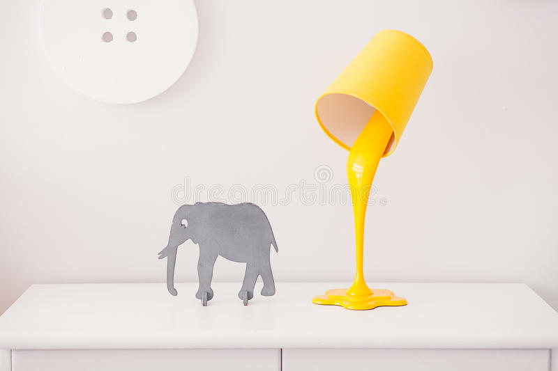 A yellow lamp in the form of a bucket of paint is on a white nightstand. Nearby is a statuette of a gray elephant. In. The background, the decor in the form of stock image