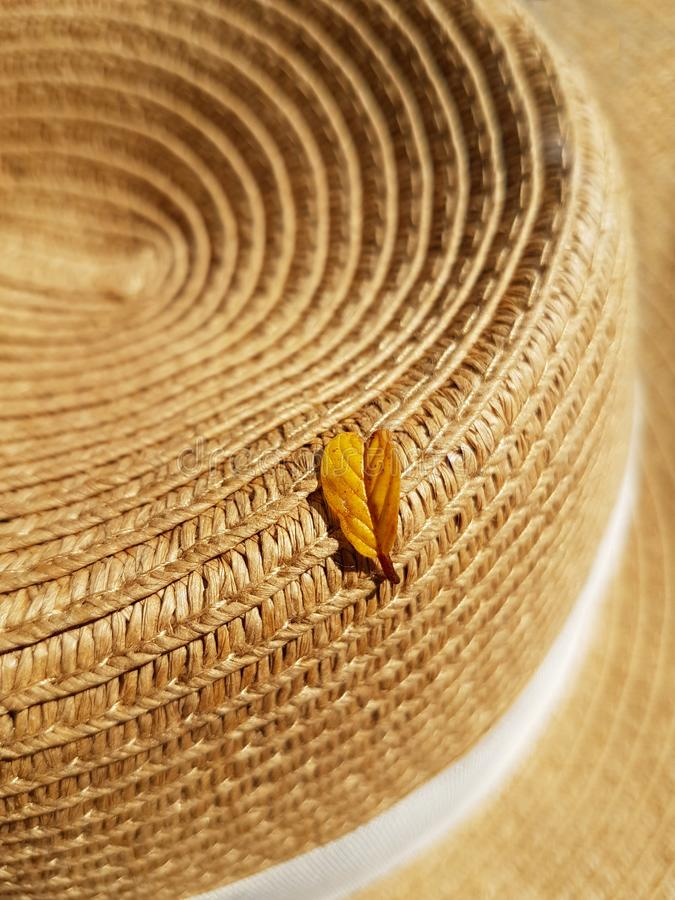 A yellow leaf fallen from a tree lies on a straw hat. Autumn concept, accessories.  stock photography