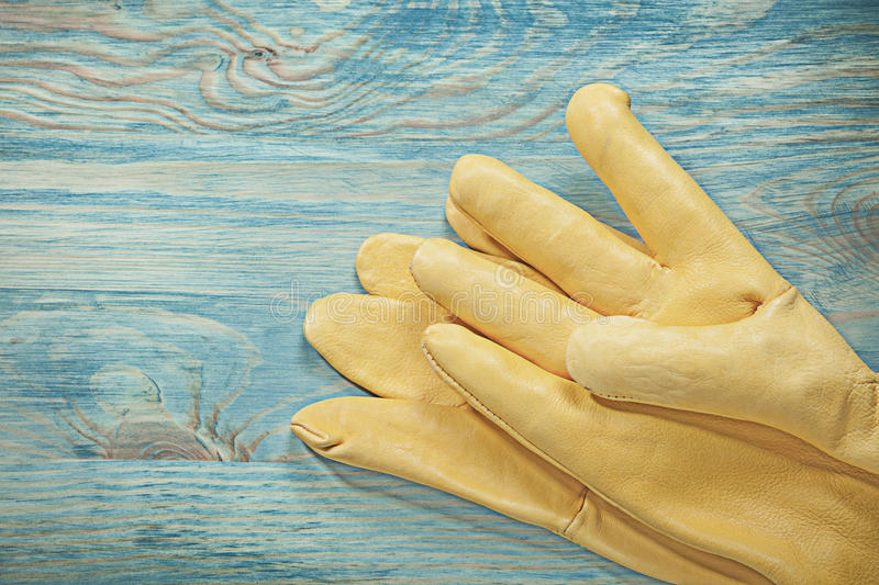 Yellow leather working gloves on wooden board construction conce. Pt stock photos